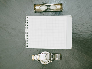 Hourglass notepad and watch lying on the table retro style