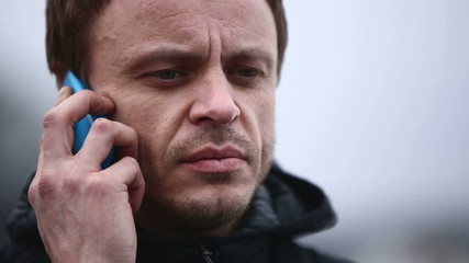 Adult serious man talking on the phone outdoors in winter
