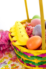 colored Easter eggs, yellow chicks and candy in a basket