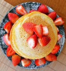 Stack of sweet pancakes with strawberry and icing sugar