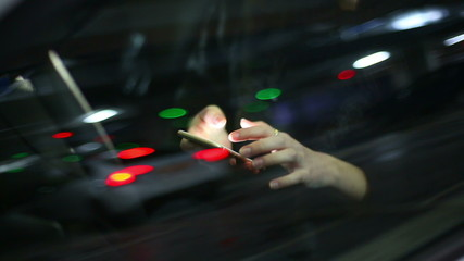 Young attractive woman using mobile phone in the car