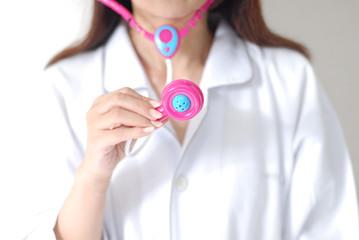 おもちゃの聴診器を手にして安心を子供に与える医療をイメージ