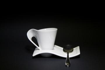 Tazzina da caffè con cucchiaino in acciaio e sfondo nero