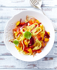 Tagliatelle pasta with peppers, red onion and basil