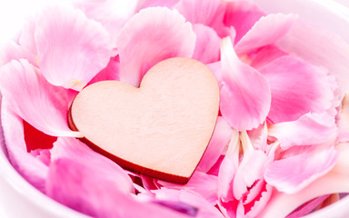 The wooden hearts on pink carnation petal.  - Concept for love a