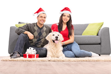 Couple with Santa hats sitting with a dog by a sofa