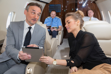 business team traveling in corporate jet and discussing a presen
