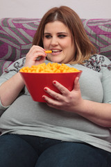 Woman eating junk food on the couch.