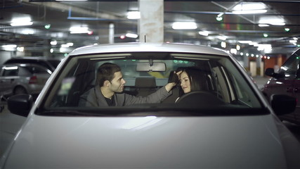 Couple embraces in the car at underground parking