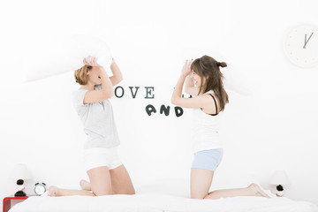 happy laughing girls having a pillow fight on the bed at home