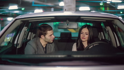 Emotions of a young couple in the car in the underground parking