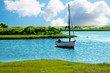 Sailboat anchored in a blue pond or lake, with green grass banks