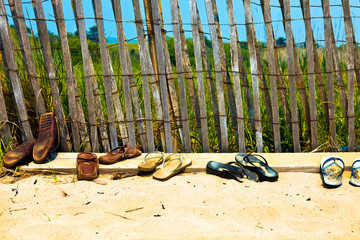 Flip flops and sandals lined up at the beach