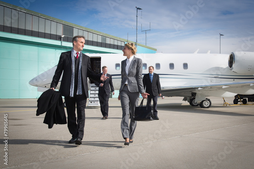 executive business team leaving corporate jet - 79965645