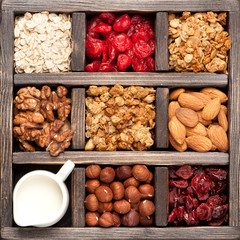 granola, oatmeal, nuts, berries in a wooden box. Top view.