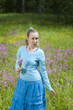 The happy young woman in the field of wild flowers