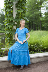 young beautiful woman in blue dress in arbor twined
