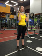 The woman trains in a gym with a bar..
