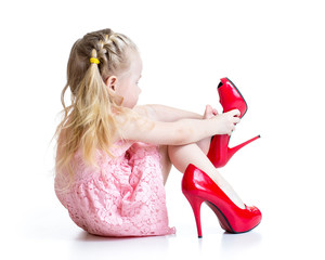 kid girl trying mummy's shoes on