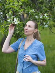 young attractive woman standing near the blossoming apple tree