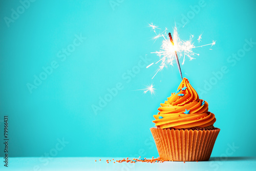 Foto Spatwand Koekjes Orange cupcake with sparkler