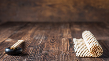 mat for sushi and chopsticks on dark wooden background.