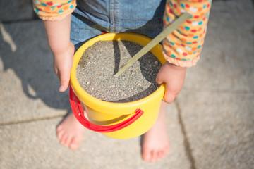 砂の入ったバケツを持つ子供