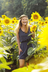 beautiful girl laughs among sunflowers