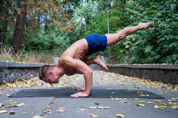 Handsome smiling flexible Athletic man doing yoga asanas in the