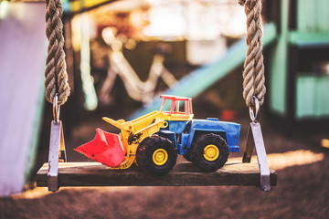 A children's excavator toy, placed on a swing at a playground.