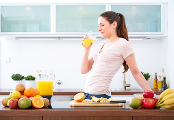 Young woman drinking a glass of orange Juice in the kitchen.III