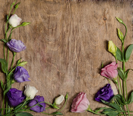 beautiful eustoma flowers with leafs and buds on wooden backgrou