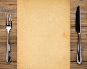 Old paper, fork and knife on wooden background