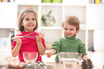 Cute little boy and girl having fun playing in the kitchen