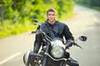 Smiling happy biker sitting on unknown big chopper bike on road - 79974438