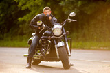 Smiling happy biker in sitting unknown on big chopper bike on ro