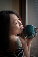 Asian woman close eyes feels positive with green cup