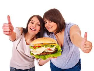 Women eating hamburger.
