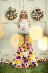 Beautiful woman in dress of flowers with birtday cake