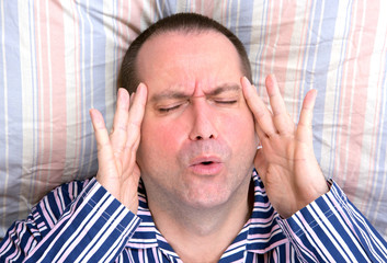 suffering man lying in bed