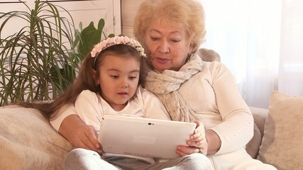 Granddaughter and her grandmother with a digital tablet at home