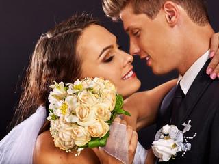 Groom embracing bride .