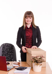 Smiling girl at office desk with a big box