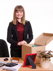 Girl standing behind an office desk with a big box