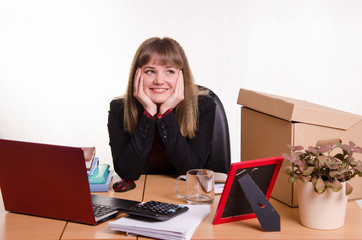 Dreamy girl sitting at office desk