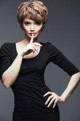Model in black dress. Fashion portrait of young woman.
