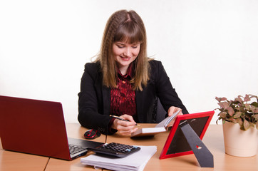 Joyful Girl sitting office desk, looking at notebook