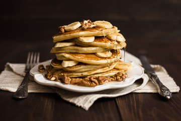 Stack of pancakes with honey, banana and walnuts