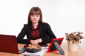 Thoughtful girl sitting at office desk