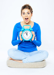 Portrait of emotional woman with open mouth holding alarm clock